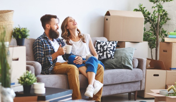 hipster couple laughing together on living room couch surrounded by boxes